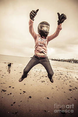 Woman Wearing Helmet And Gloves Jumping On Beach Poster