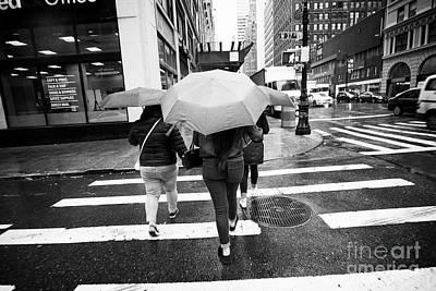 women  holding umbrellas cross a wet city street during rain shower midtown New York City USA Poster