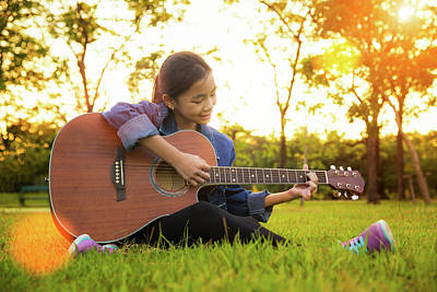 Young Artist Play Solo Guitar In Green Nature Park Poster by Anek Suwannaphoom