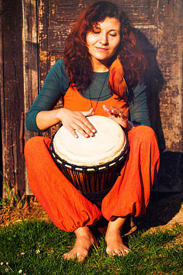 Young Barefoot Lady Drummer Playing On Her Djembe Drum On Rustic Wooden Door Background. Poster by Jozef Klopacka