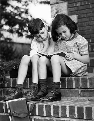 Young Boy & Girl Reading A Book Outdoors Poster