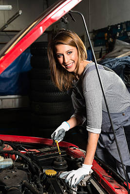 Young Female Trainee Fixing Car Engine In Garage Poster