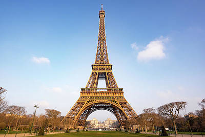 Photograph - Eiffel tower against blue sky in orange morning light by Philippe Lejeanvre