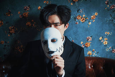 Photograph - Young Chinese man holding a mask portrait by Philippe Lejeanvre