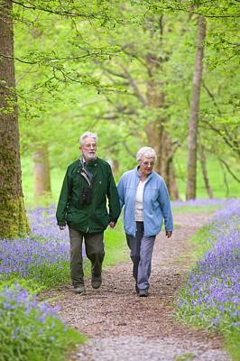 Blue Glass Photograph - An Elderly Couple Walking by Ashley Cooper