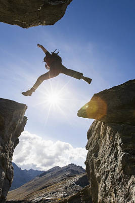 Backlit View Of Hiker Leaping Between Art Print