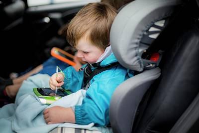 Candid Photograph - Boy In Car Using Digital Device by Samuel Ashfield