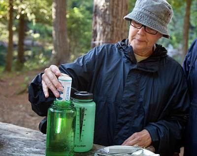 Camper Using A Uv Water Purifier Art Print by Jim West