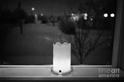candle in the window looking out over snow covered scene in small rural village of Forget Saskatchew Art Print by Joe Fox