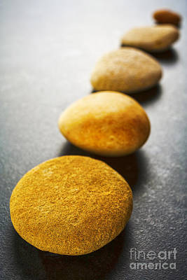 Diagonal Line Of Brown Pebbles On Dark Background Art Print by Colin and Linda McKie