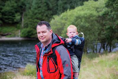 Great Outdoors Photograph - Father Carrying Son In Back Carrier by Samuel Ashfield