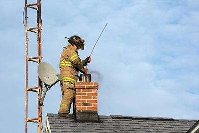 Fire Fighter Photograph - Firefighter Fighting A Chimney Fire by Jim West
