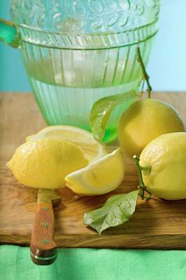 Water Jug Photograph - Fresh Lemons With Leaves In Front Of Water Jug by Foodcollection