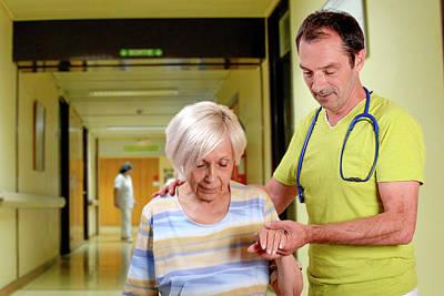 Hospital Doctor Assisting Elderly Woman Art Print by Aj Photo