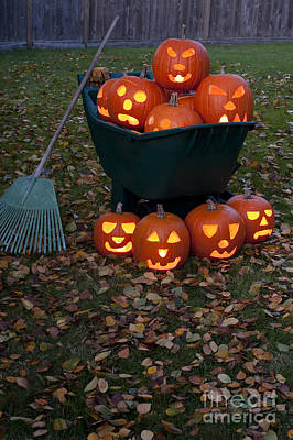 Photograph - Lit Carved Pumpkins In Wheelbarrow by Jim Corwin