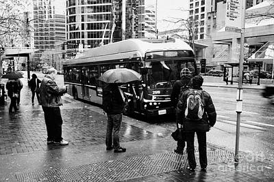 people standing in the rain waiting for a bus on burrard street downtown Vancouver BC Canada Print by Joe Fox