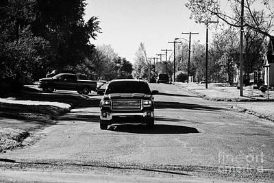 pickup trucks driving through street in small town in rural Saskatchewan Canada Art Print by Joe Fox