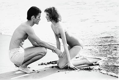 Rene Russo With A Man On A Beach Art Print by Francesco Scavullo