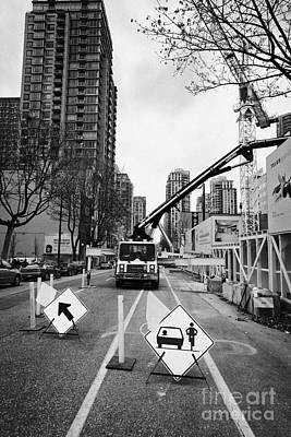 road closed to traffic to allow large articulated crane operate at building site Vancouver BC Canada Art Print by Joe Fox