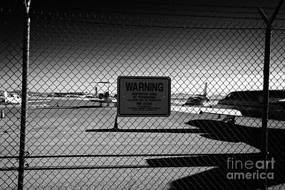 security chain link fencing with warning restricted area sign on the perimeter of mccarran airport L Art Print
