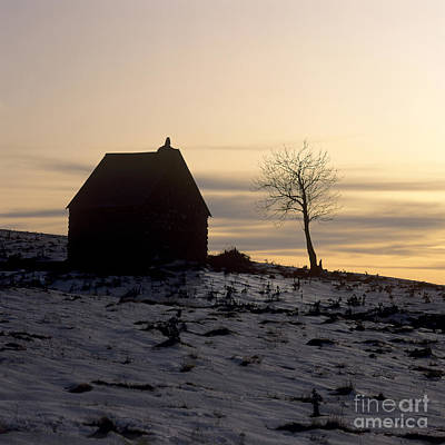 Snow Covered Fields Photograph - Silhouette Of A Farm And A Tree. Cezallier. Auvergne. France by Bernard Jaubert
