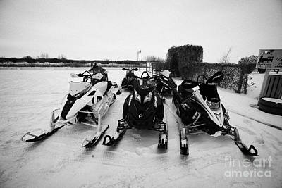 Sask Photograph - snowmobiles parked in Kamsack Saskatchewan Canada by Joe Fox