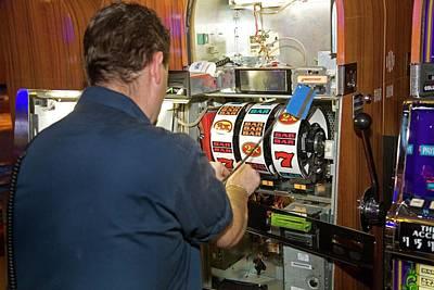 Technician Servicing A Slot Machine Art Print by Jim West