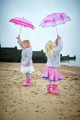 Two Girls On Beach Holding Umbrellas Art Print by Ruth Jenkinson