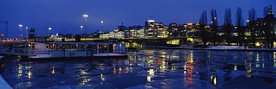 Island Light Photograph - Buildings In A City Lit Up At Night by Panoramic Images