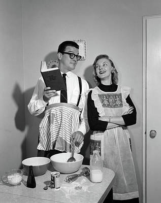 Cookbooks Photograph - 1950s Couple In Kitchen With Husband by Vintage Images