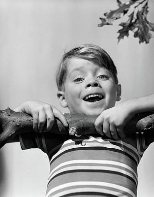 Chin Up Photograph - 1950s Smiling Boy Doing Chin-up On Tree by Vintage Images