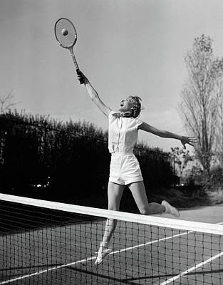 Clothes Clothing Photograph - 1950s Woman Jumping To Hit Tennis Ball by Vintage Images