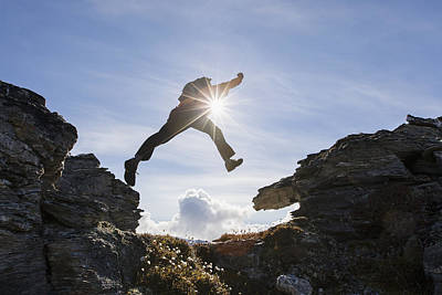 Backlit View Of Hiker Leaping Between Art Print by Scott Dickerson