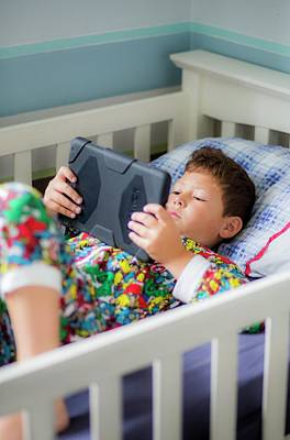 Boy In Bed Using A Digital Tablet Art Print by Samuel Ashfield