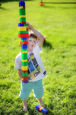 Boy Playing With Plastic Bricks Art Print by Samuel Ashfield