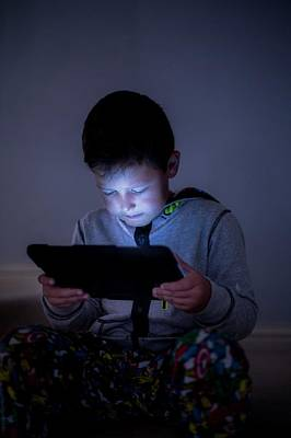 Boy Using A Digital Tablet In The Dark Art Print by Samuel Ashfield