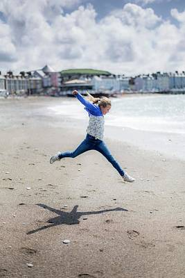 Great Outdoors Photograph - Girl Leaping On Beach by Samuel Ashfield