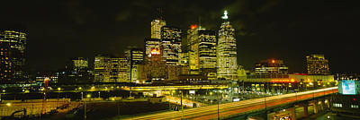 Buildings In A City Lit Up At Night Art Print by Panoramic Images