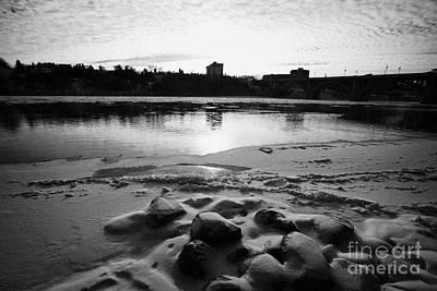 frozen river bank of the south saskatchewan river in winter flowing through downtown Saskatoon Saska Art Print by Joe Fox