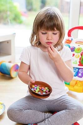Girl Sitting On Floor With Bowl Of Sweets Art Print by Aberration Films Ltd