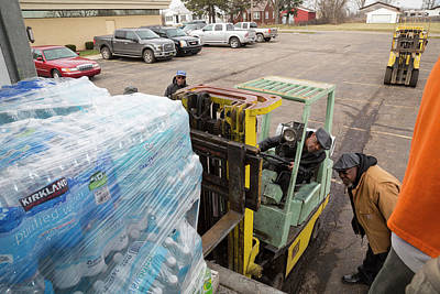 Delivering Photograph - Flint Bottled Drinking Water Distribution by Jim West