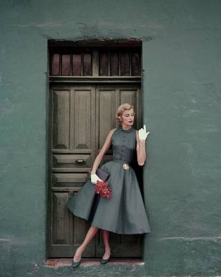 Textile Photograph - A 1950s Model Standing In A Doorway by Leombruno-Bodi