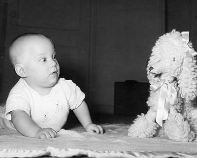 A Baby And A Toy Dog Print by Orville Andrews