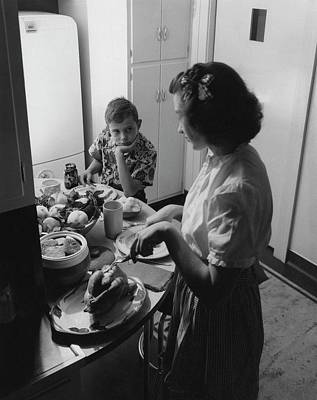 Tableware Photograph - A Boy Watching His Mother Prepare Dinner by Luis Lemus