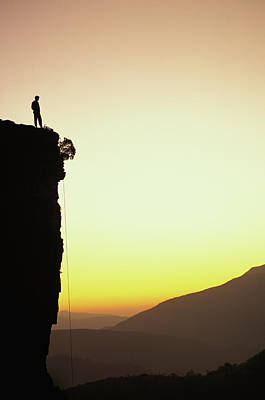 Sunrise Photograph - A Climber Stands Atop A Cliff by Bill Hatcher