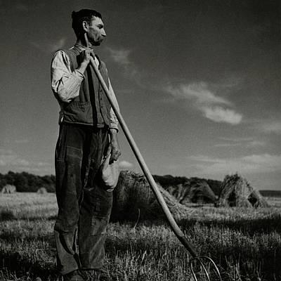Landscape Photograph - A Farmer Holding A Pitchfork by Roger Schall