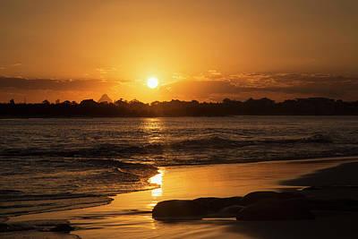 A Golden Sun Sets Over Silhouetted Art Print by John Short