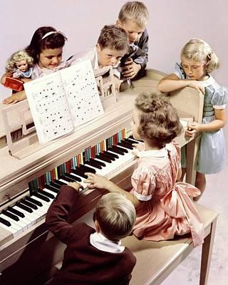 A Group Of Children At The Piano Art Print by Herbert Matter