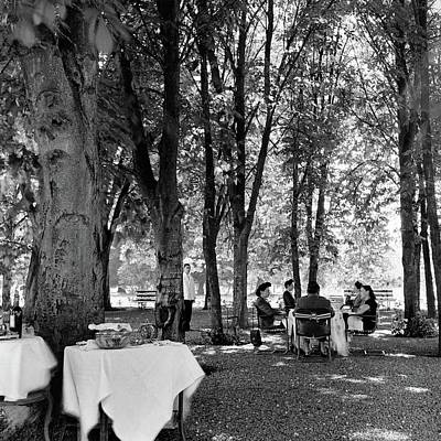 A Group Of People Eating Lunch Under Trees Art Print