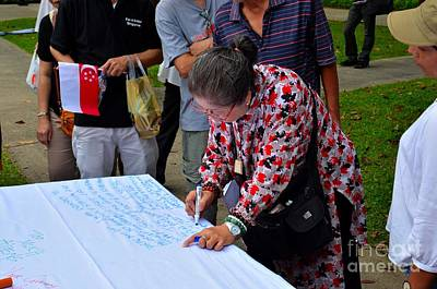 A Lady Signs Petition At May Day Rally Singapore Original by Imran Ahmed